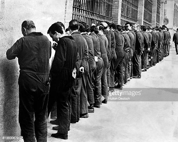 Because going on strike is against the law these Spanish factory workers protest by spending their lunch break facing the factory wall | Location...