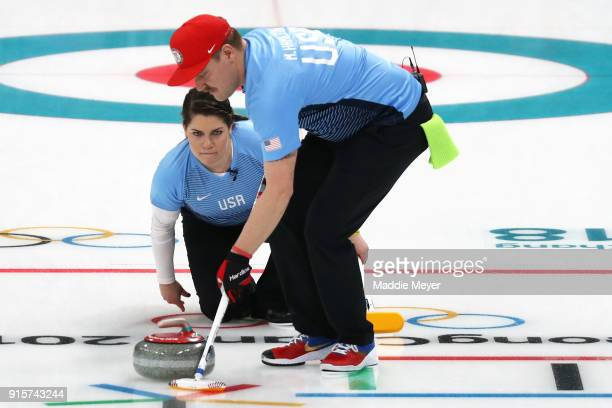 Becca Hamilton delivers a stone against Canada as Matt Hamilton of the United States of America sweeps the ice in the Curling Mixed Doubles Round...