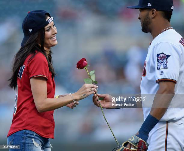 Becca Kufrin from The Bachelorette takes a rose from Eddie Rosario of the Minnesota Twins after she delivered a ceremonial pitch before the game...