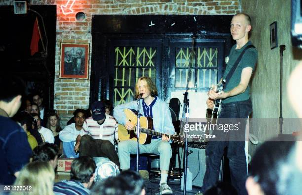 Beck performs with Chris Bellew on bass, Bellew smiles to the camera, percussion on plastic water jug, at Troy Cafe in Little Tokyo, co-owned by...