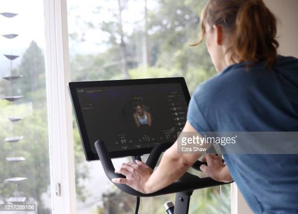 Becky Friese Rodskog rides her Peloton exercise bike at her home on April 06, 2020 in San Anselmo, California. More people are turning to Peloton due...