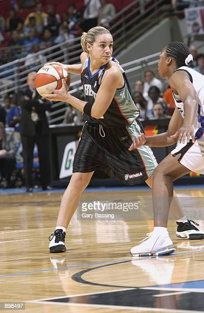 Becky Hammon of the New York Liberty holds the ball away from Elaine Powell of the Orlando Miracle in the game on June 23 2002 at TD Waterhouse...