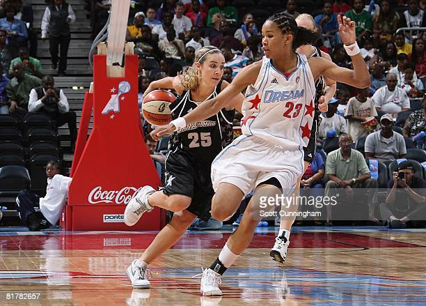 Becky Hammon of the San Antonio Silver Stars drives down the court against Tamera Young of the Atlanta Dream during the WNBA game on June 18 2008 at...