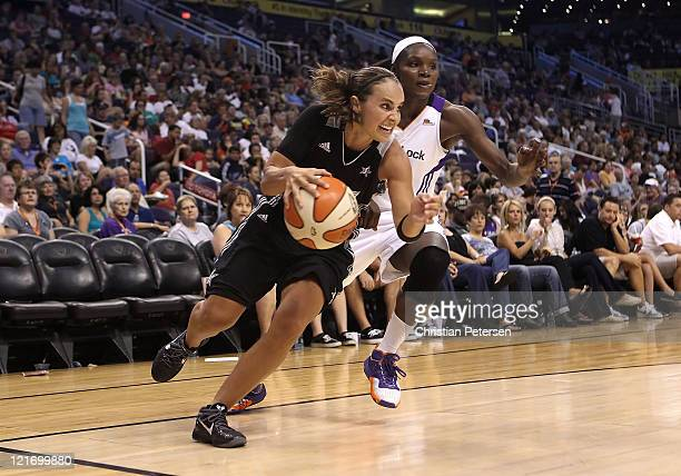 Becky Hammon of the San Antonio Silver Stars drives the ball past Marie FerdinandHarris of the Phoenix Mercury during the WNBA game at US Airways...