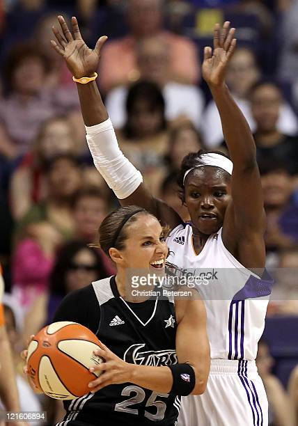 Becky Hammon of the San Antonio Silver Stars handles the ball under pressure from Marie FerdinandHarris of the Phoenix Mercury during the WNBA game...