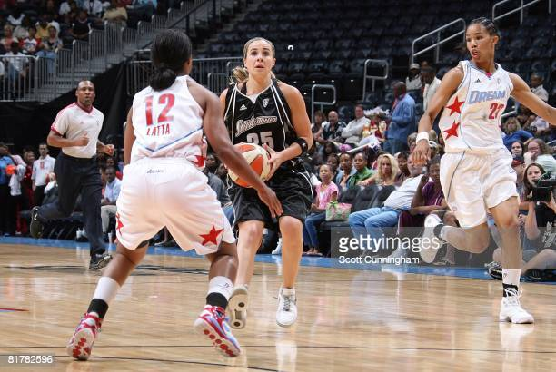 Becky Hammon of the San Antonio Silver Stars looks for the shot against Ivory Latta and Tamera Young of the Atlanta Dream during the WNBA game on...