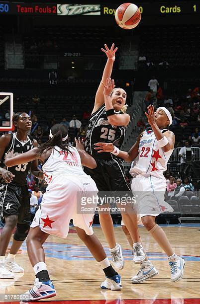 Becky Hammon of the San Antonio Silver Stars passes the ball under pressure against Betty Lennox and Camille Little of the Atlanta Dream during the...