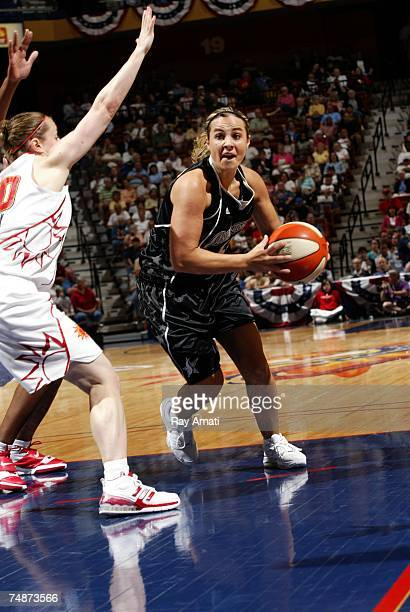 Becky Hammon of the San Antonio Silver Stars shoots against Jamie Carey of the Connecticut Sun on June 23 2007 at Mohegan Sun Arena in Uncasville...
