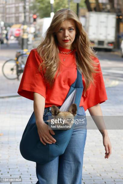 Becky Hill carries her pet dog as she leaves Capital Breakfast Radio Studios on September 22, 2021 in London, England.