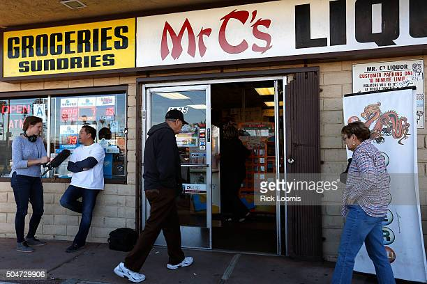 SAN PEDRO CA TUESDAY JANUARY 12 2016 Becky Sullivan of NPR interviews Kenneth Chan of Mr C's Liquor in San Pedo Ca while people file in to purchase...