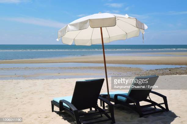 bed beach and white umbrella on tropical beach with blue sky in the summer morning. - aungsumol stock pictures, royalty-free photos & images