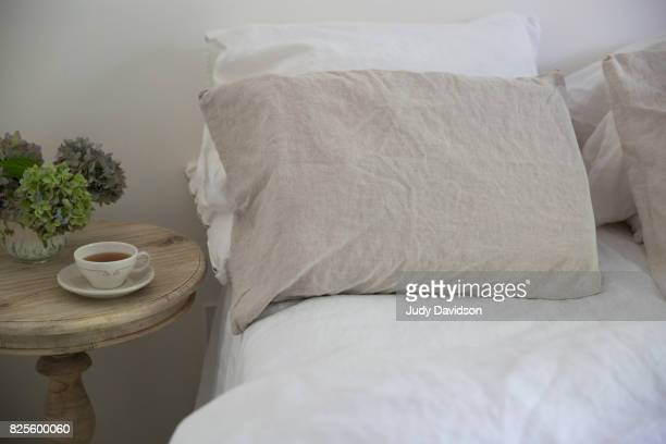 Bed, cup of tea and bedside table with flowers
