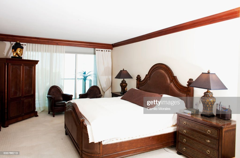 Bed, dressers and windows in ornate bedroom : Foto stock