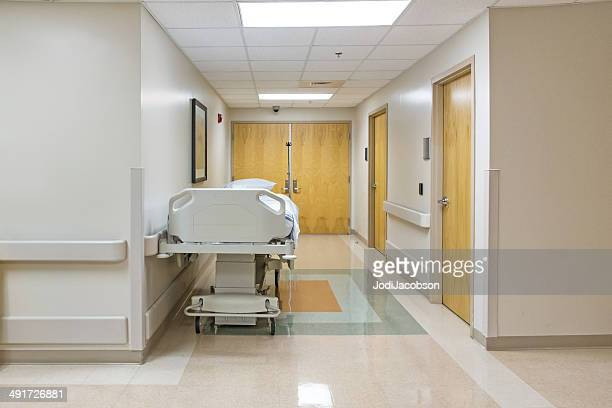 Bed in empty hospital corridor