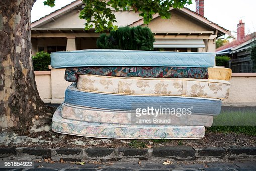 bed mattresses left out for collection on suburban street