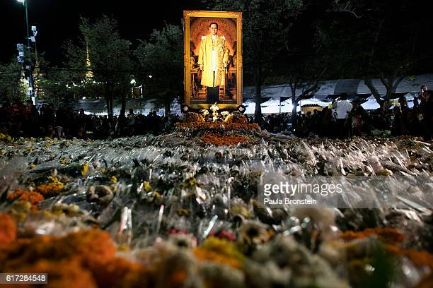 A bed of flowers from mourners is seen by a portrait of the late King on October 22 2016 in Bangkok Thailand Tens of thousands attended the emotional...