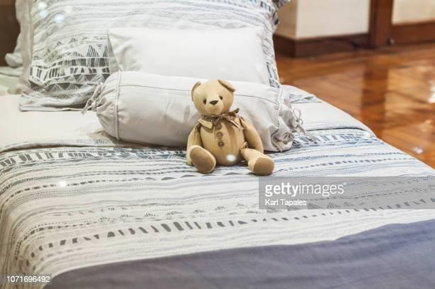 A bed with a teddy bear