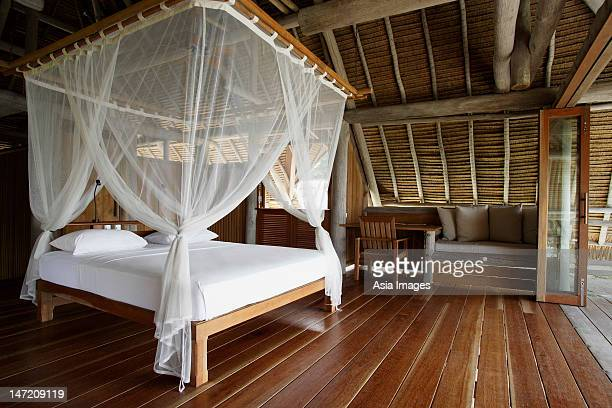 bed with net curtain - mosquito net stock photos and pictures