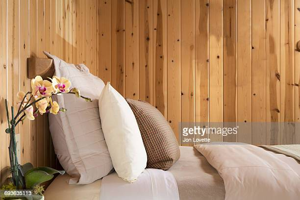Bed with Orchid and Wood Paneled Wall