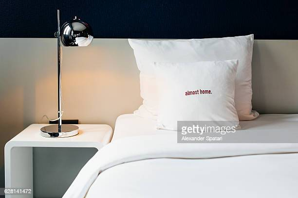 Bed with white linens and a nightstand with lamp in a hotel