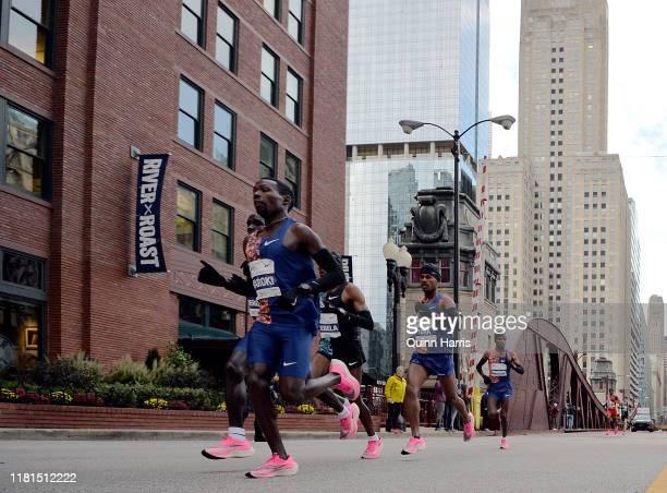 Bedan Karoki of Kenya runs in front of Dejene Debela of Ethiopia, Seifu Tura of Ethiopian, and Lawrence Cherono of Kenya during the 2019 Bank of...