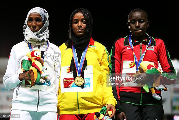 Bedatu Hirpa of Ethiopia gold medal celebrates with Dalila Abdulkadir Gosa of Bahrain silver medal and Joyline Cherotich of Kenya bronze medal on the...