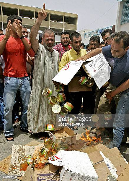 Palestinian refugees who fled the besieged refugee camp of Nahr alBared in north Lebanon throw canned food during a protest in the adjacent refugee...