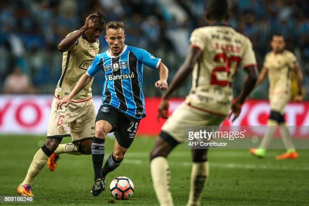 Beder Caicedo of Ecuador's Barcelona vies for the ball with Arthur of Brazil's Gremio during their Copa Libertadores 2017 football match held at the...
