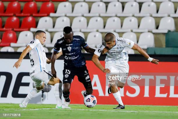 Beder Caicedo of Independiente del Valle fights for the ball with Felipe and Darlan Mendes of Gremio during a third round first leg match between...