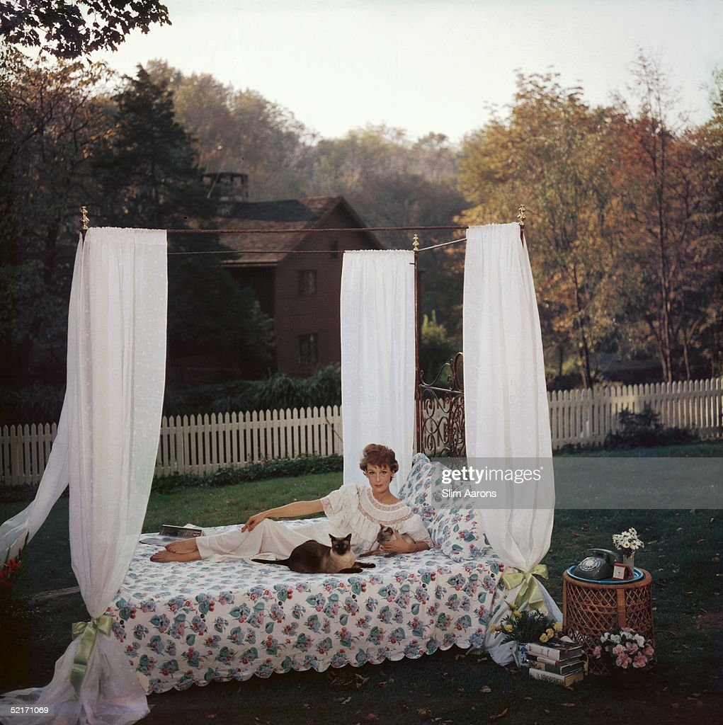 Bedford, New York resident Mary Jane Russell poses with her cats on a four-poster style bed laid out on the lawn, 1960.