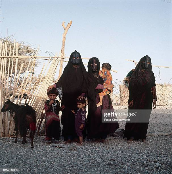 Bedhouin women wearing black burkas and traditional facemasks and their children stand near a fence around an enclosure where they keep their...