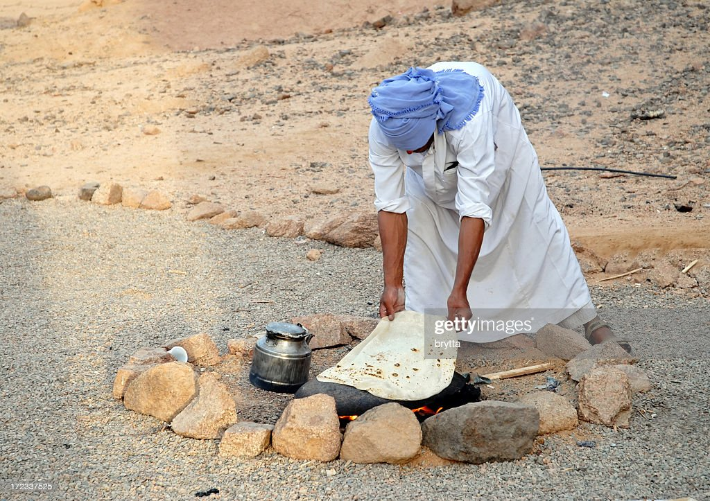 Bedouin baking bread on hot stone, Sinai Desert,Egypt : Stock Photo