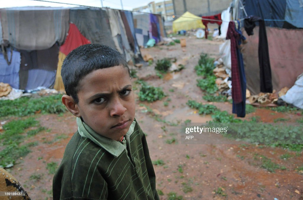 A Bedouin boy from Syria, whose family have taken refuge for the winter in Lebanon, is seen walking across muddy tracks at their camp close to the village of Kfarkahel, in the Koura district near the northern city of Tripoli on January 9, 2013, as stormy weather sparked widespread flooding, prompting chaos on the roads and a nationwide school closure. The number of Syrian refugees in Lebanon is already totaling 156,000, according to UN figures, and 200,000 according to the Lebanese government estimates.