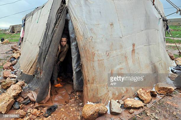 A Bedouin child from Syria who has taken refuge with his family for the winter in Lebanon stands inside a tent close to the village of Kfarkahel in...