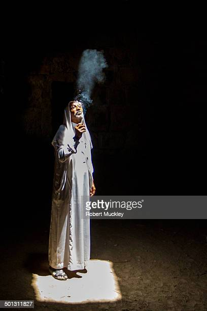 CONTENT] A bedouin dressed in traditional clothes stands in a shaft of light deep in Kerak castle exhaling reflected smoke into the darkness