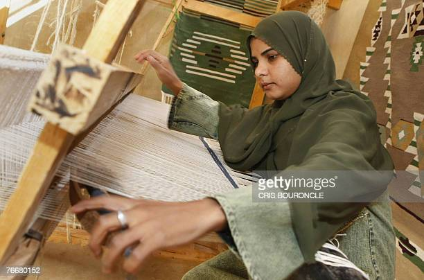 A Bedouin girl operates a loom fabricating traditional Kallim rugs at the alHayah community cooperative in the ElFarafra Oasis 460 kilometers...