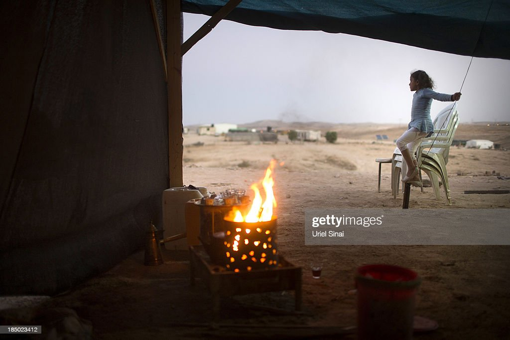 A Bedouin girl plays outside a tent on October 9, 2013 in the Bedouin village of Al-Arakib, Israel. Roughly 200,000 Bedouins live in the Negev desert, with about half living in the seven Israeli government built townships in the northeast of the Negev and half in unrecognized villages, which lack basic services such as clean water, electricity or sanitation. The Israeli Parliament (Knesset) is set to bring a final vote on the Prawer-Begin Bill during its winter session, which starts this week. If implemented the law would forcibly displace tens of thousands of Arab Bedouin citizens living in the unrecognized villages and see them settled in the seven Bedouin townships. The Negev Bedouin tribes have vowed to fight the proposed law, which they argue will dispossess them of their homes and force a final settlement to their claims of historical rights to the land.