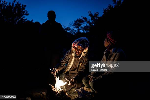 A bedouin guide sits in front of the fire while leading tourists hiking through the mountains of South Sinai on April 17 2015 near St Catherine Egypt...