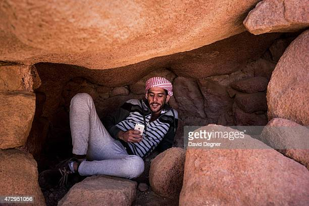 Bedouin guide takes a break in a cave to check messages and take photos while leading tourists hiking through the mountains of South Sinai on April...