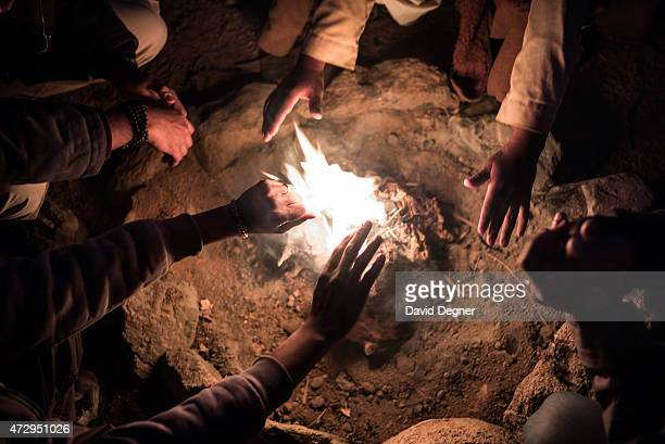 Bedouin guides warm their hands around the fire at night while leading tourists hiking through the mountains of South Sinai on April 17 2015 near St...