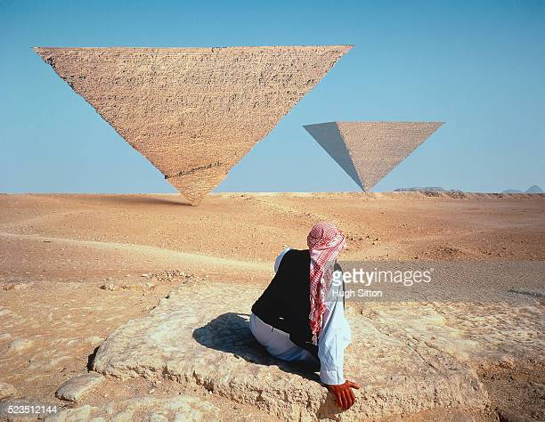 bedouin in desert and pyramids upside down, symbolic - hugh sitton stock pictures, royalty-free photos & images