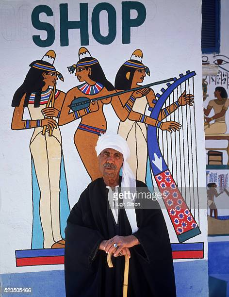 bedouin man standing in front of souvenir shop sign, luxor, egypt - hugh sitton stock pictures, royalty-free photos & images