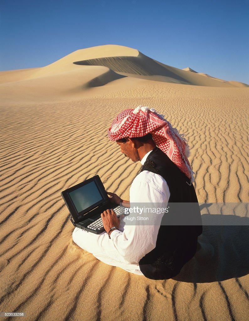 Bedouin man using laptop computer, Sahara desert, Egypt, Africa : Stock Photo