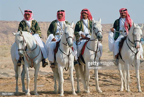 Bedouin men riding horses in the desert inSaudi Arabia
