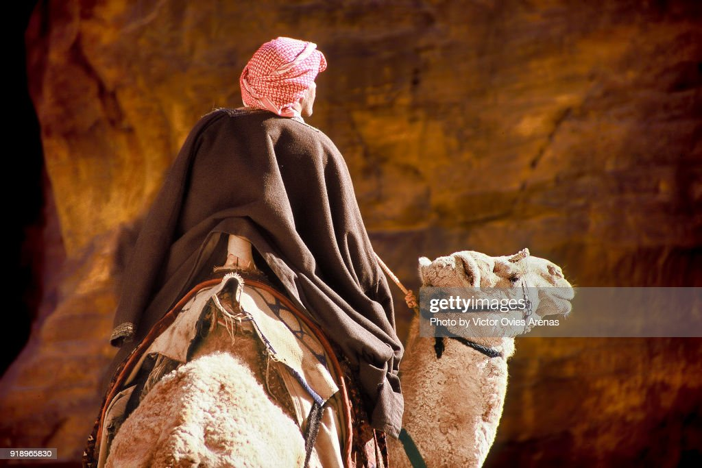 Bedouin on a camel in the narrow defile of Bab al Siq in Petra, Jordan : Foto de stock