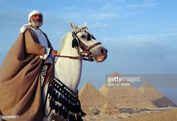 Bedouin on horseback in front of the pyramids of Cheops Chephren and Menkaure Giza Plateau Egypt