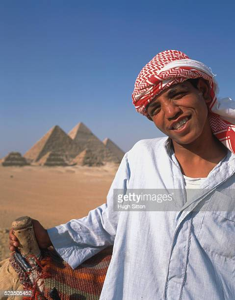 bedouin rider and camel in front of pyramids - hugh sitton stock-fotos und bilder