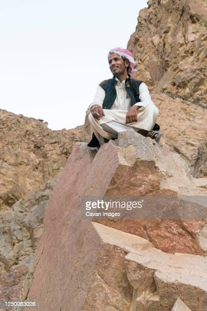 a bedouin sitting in a rock in the mountains near nuweiba - bedrock stock pictures, royalty-free photos & images