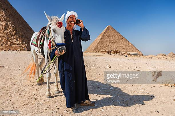 Bedouin using phone, pyramids on the background
