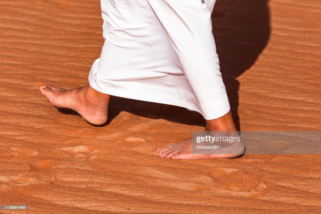 Bedouin walking in the desert, Wahiba Sands, oman : Stock Photo